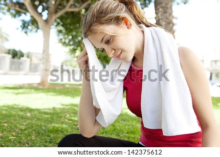 Young attractive woman relaxing from doing exercise in a city park, sitting down and drying her forehead sweat with a white towel during a sunny morning. - stock photo