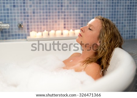Young attractive woman relaxing in hot bath - stock photo