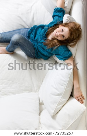 Young attractive woman relaxing on white sofa - stock photo