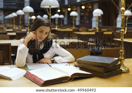Young attractive woman sitting at desk in old university library studying books. - stock photo