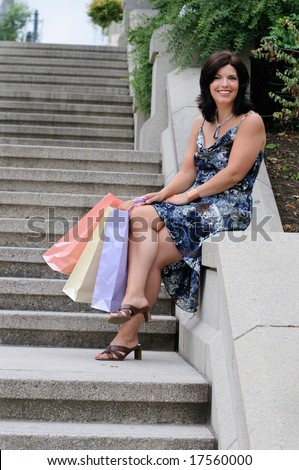 Young Attractive Woman Sitting Down To Rest Her Feet From Shopping - stock photo