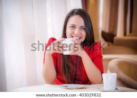 young attractive woman sitting in a cafe with a coffe