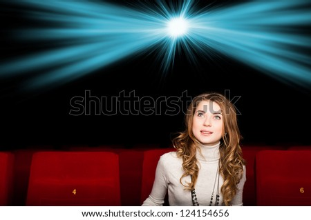 young attractive woman sitting in a cinema, enjoying a movie - stock photo