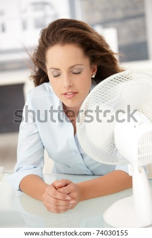 Young attractive woman sitting in office front of fan, feeling hot, cooling herself, eyes closed.? - stock photo