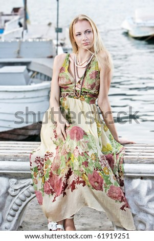 young attractive woman sitting on pier background - stock photo