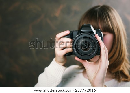 Young attractive woman smiling and holding a vintage camera - stock photo