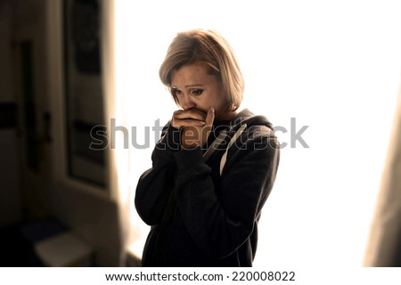 young attractive woman suffering depression and stress standing alone crying in pain and grief against window feeling sad and desperate at home with studio backlight - stock photo