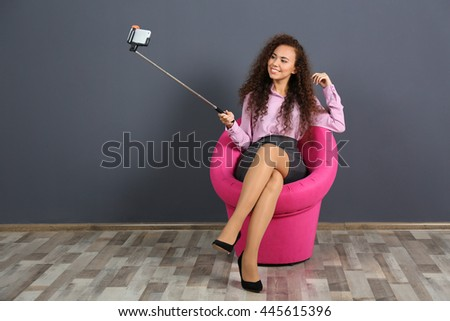 Young attractive woman taking selfie on pink chair in the room - stock photo
