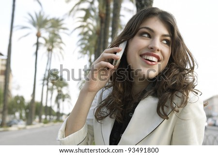Young attractive woman talking on a cell phone in a tree aligned street. - stock photo
