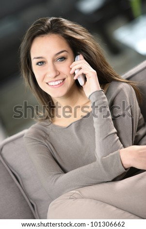 young attractive woman talking on the telephone at home - stock photo