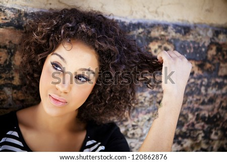 Young attractive woman thoughtful on urban background - stock photo