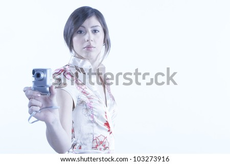 Young attractive woman using a digital photo camera on a plain background. - stock photo