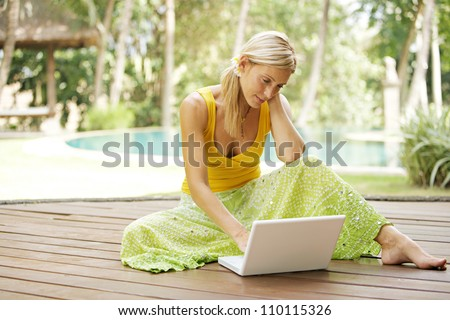Young attractive woman using a laptop computer while laying down on a wood deck in a tropical garden while on vacation. - stock photo