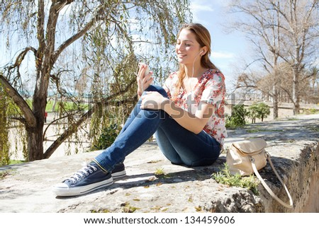 Young attractive woman using a smartphone to listen to music while sitting on a stone wall high up in a park with a blue sky during a sunny day. - stock photo
