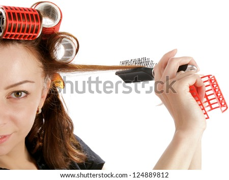 Young Attractive Woman Using Curlers with Hairbrush closeup on white background