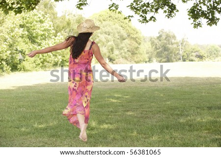 young attractive woman walking away from camera with arms outstretched