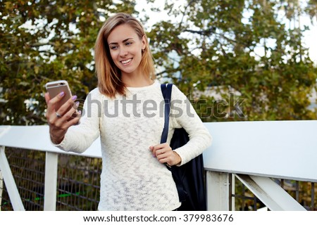 Young attractive woman wanderer smiling while making photo via smart phone camera for social network, charming happy female traveler photographing herself on cell telephone while standing outdoors - stock photo