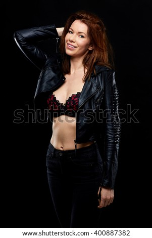 Young attractive woman wearing black leather jacket over her bra, shoot over black background - stock photo