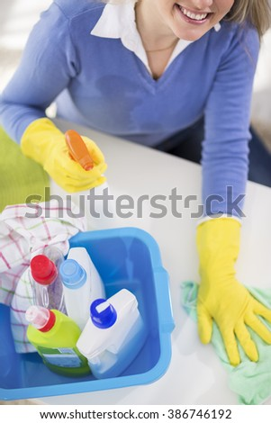 Young attractive woman wipe table and cleans room - stock photo
