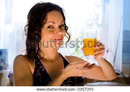 Young attractive woman with a glass of fresh squeezed orange juice.