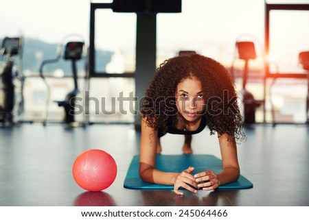 Young attractive woman with curly hair leaning on her elbows working out at gym - stock photo