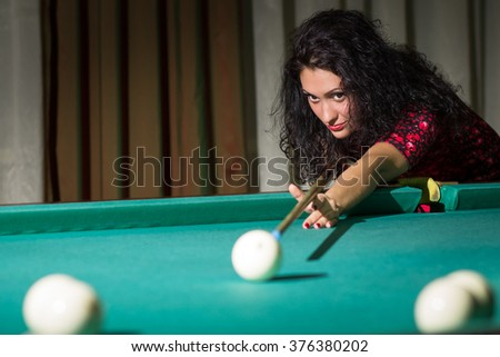 Young attractive woman with dark frizzy hair hitting ball with cue playing billiards. Pool game background  - stock photo