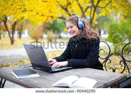 young attractive woman with headphones and laptop computer in park - stock photo