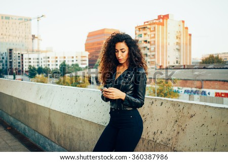 young attractive woman with long curly hair wearing a black leather jacket  using smartphone outdoors. pretty female student chatting online on her smart-phone - stock photo