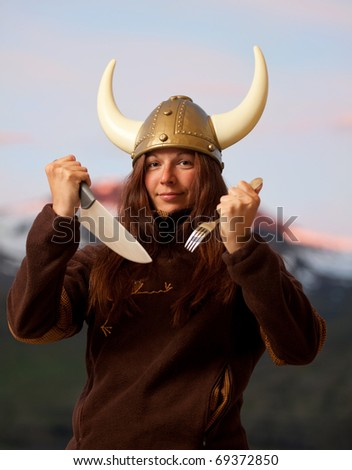 young attractive woman with nordic helmet posing with knife and fork