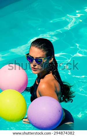 young attractive woman with sunglasses and balloons in the  pool - stock photo