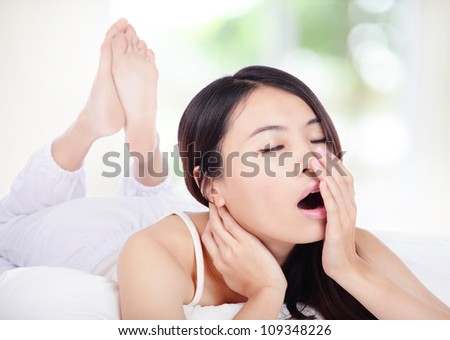 young attractive woman yawning in bed in the morning with nature green background, model is a asian girl - stock photo