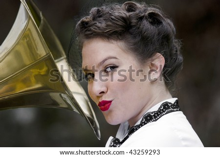 Young attractive women dressed in forties style kissing gramophone. - stock photo
