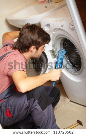 Young attractive worker in uniform fixing washing machine, background - stock photo