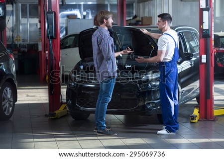 Young automotive technician talking with male client - stock photo
