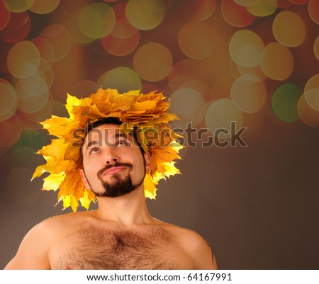 Young autumn man wearing leaves hat.