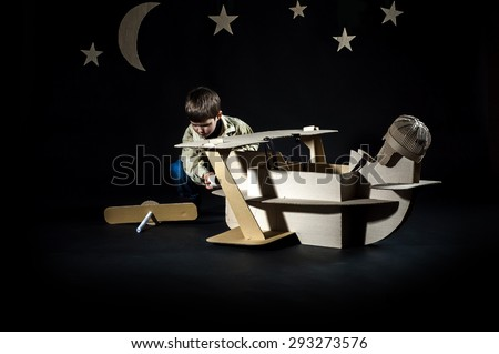 Young aviator assembling corrugated plane on the dark night sky background.