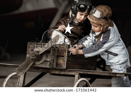 Young aviators in homemade aircraft in a large hangar - stock photo