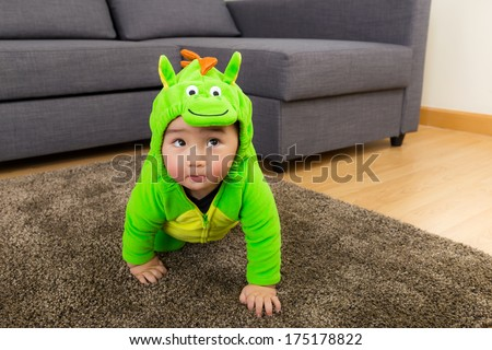 Young baby boy dressed in dinosaur - stock photo