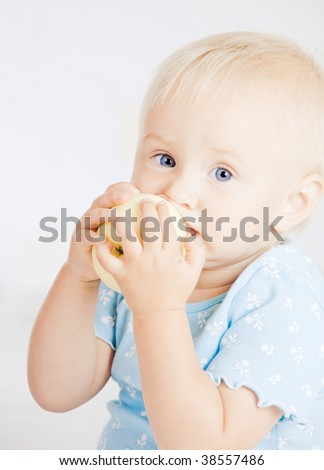 Young baby eating a yellow apple