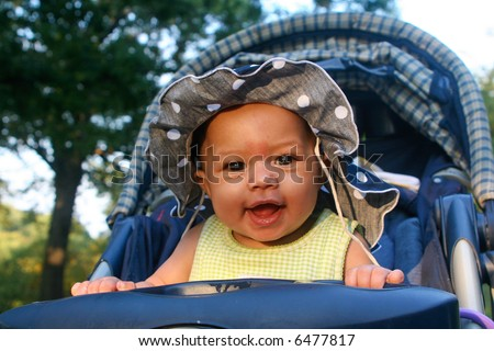 Young baby girl enjoying ride in her stroller