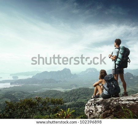 Young backpackers enjoying a valley view from top of a mountain