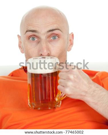 Young bald headed man drinking glass of beer with frothy head; isolated on white background. - stock photo