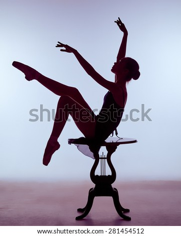 young ballerina in a blue dress sitting on wooden chair on a lilac background. Ballerina is wearing in pointe shoes.  The outline shooting - silhouette of girl  - stock photo