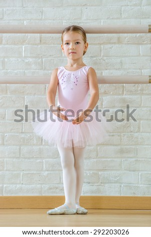 Young ballerina in pink clothes is standing at a ballet class. - stock photo