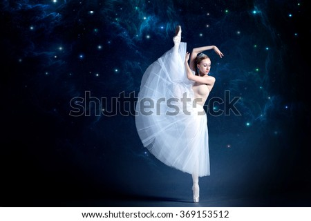 Young ballerina is dancing with the starry night sky in the background. Girl is wearing a beautiful dress that adds a romantic and wondering atmosphere to the photo. - stock photo