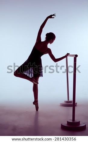 young ballerina stretching on the bar on blue background. The outline shooting - silhouette of girl - stock photo