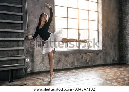 Young ballet dancer - Harmonious pretty woman posing in studio - stock photo