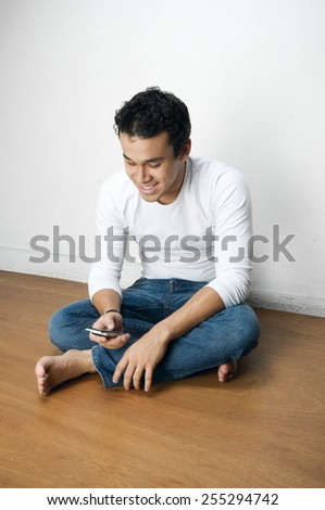 Young barefoot man in various poses on a  wooden floor next to a wall
