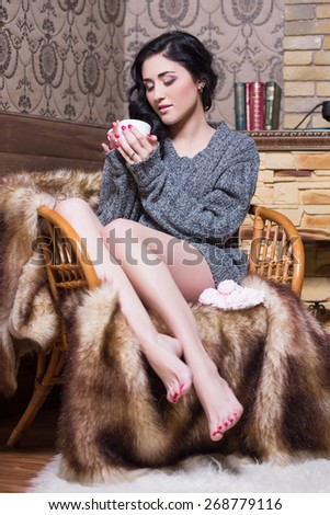 Young barefoot woman sitting on the chair with a cup - stock photo