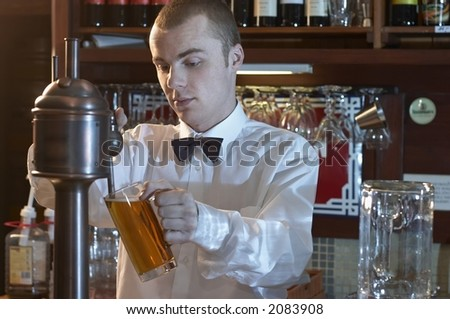 young barman at a bar counter pouring beer - stock photo